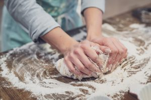 person standing and making dough
